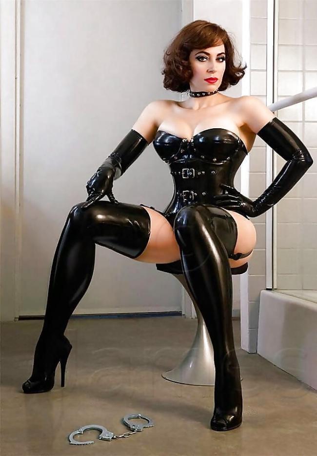 бдсм девушка в черном костюме из латекса, нарукавники, чулки, ошейник, на полу лежат наручники