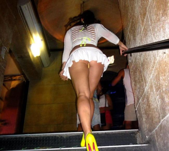 Поднимается по лестнице в короткой юбке