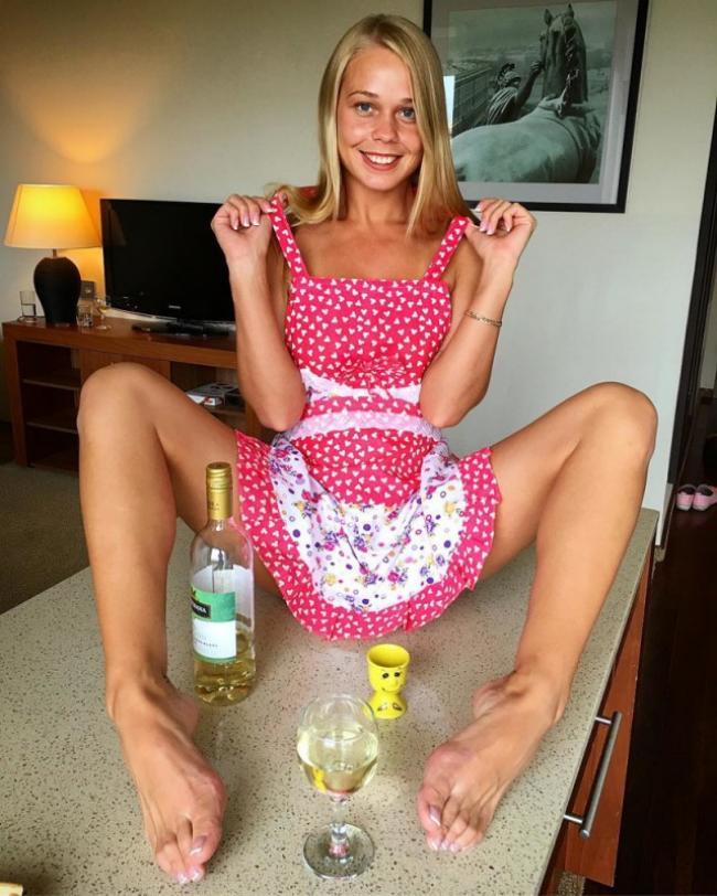 Блондинка в коротком розовом платье на столе сидит показывая стопы.