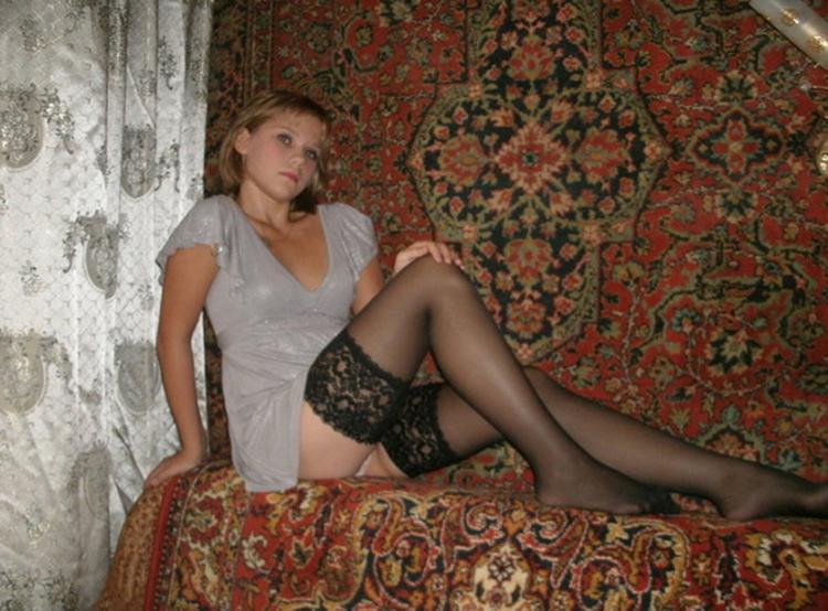 Симпатичная девушка сидит на диване в коротеньком простом платье и черных чулках