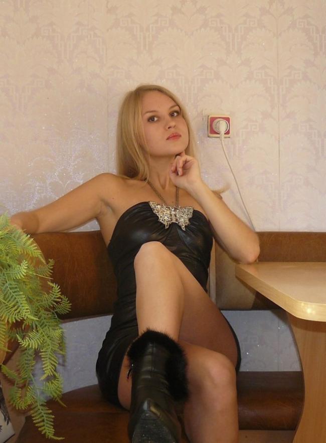 Шикарная блондинка в коротеньком черном платье и сапожках сидит за столом.