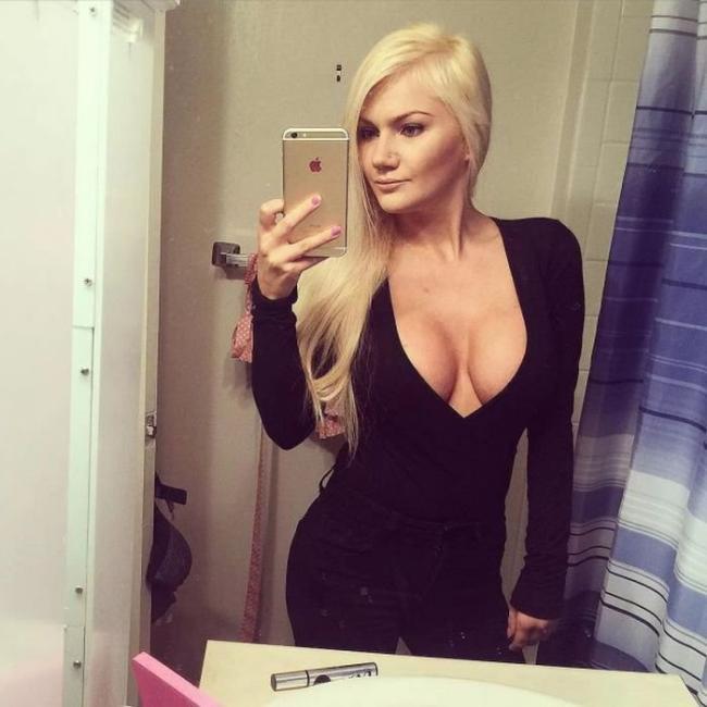 Блондинкап в черном облегающем платье с глубоким декольте.