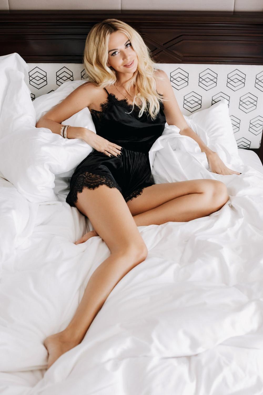 Виктория Лопырева фото в черном коротком пеньюаре на кровати лежит показывая свои красивые ножки