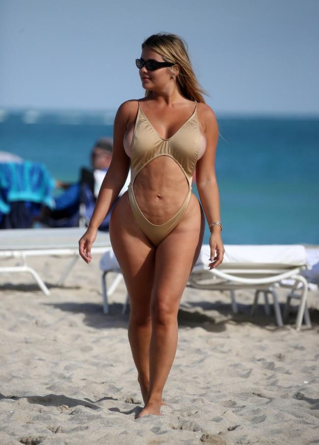 зрелые женщины в купальниках на пляже фото красавица с шикарными формами идет по пляжу, волосы распущены, голова повернута вправо, на глазах надеты большие черные солнцезащитные очки, позади видны лежаки, на заднем плане море.