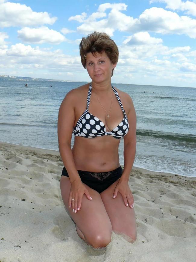 зрелые женщины в купальниках фото красивая тетя с хорошей фигурой сидит на коленях в песке на берегу моря, руки положила на бедра, волосы светлые, стрижка короткая.