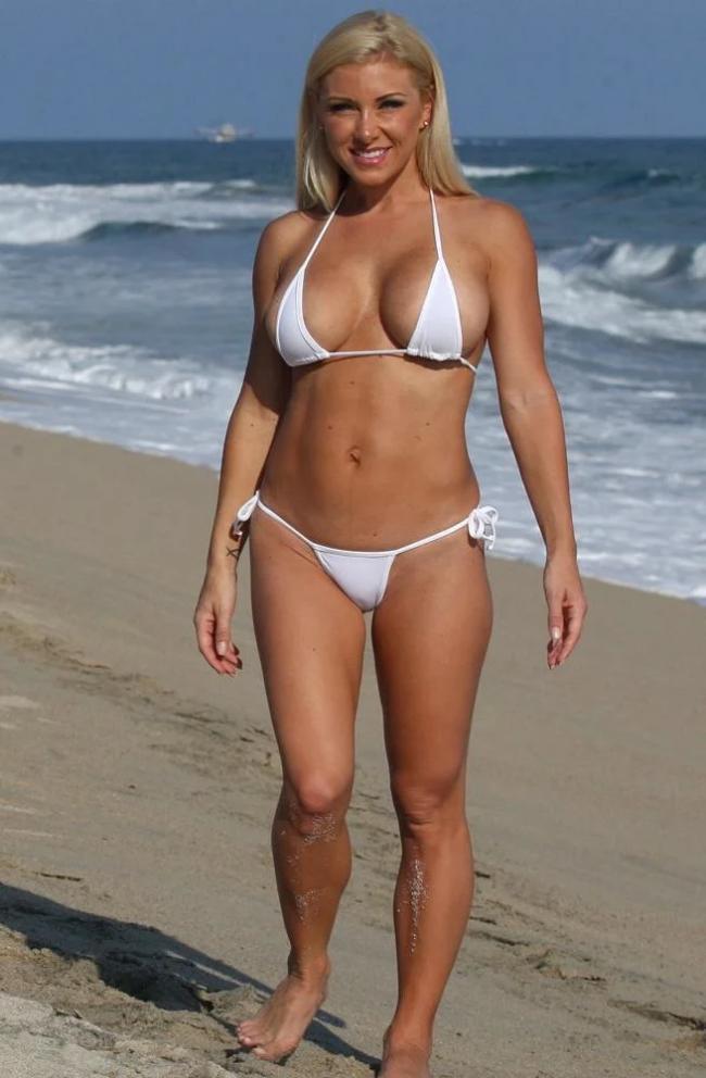 зрелые женщины в купальниках на пляже, красивая блондинка в белом купальнике бикини стоит на берегу моря, ноги на ширине плеч, руки лежат вдоль тела, широко улыбается, волосы распущены, на заднем плане видно волнующееся море.