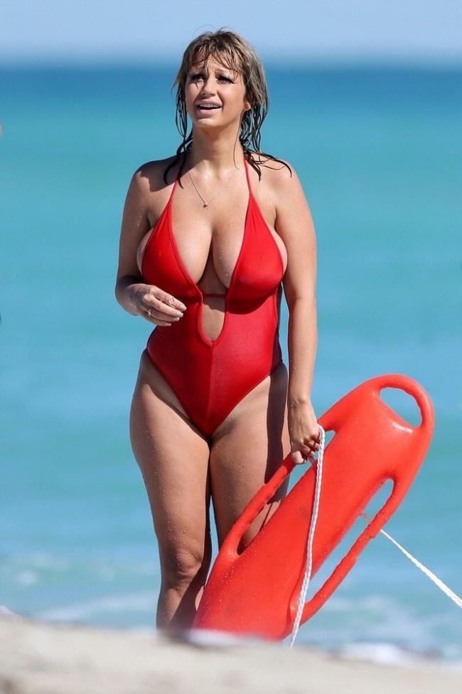 Красивая зрелая женщина с шикарной фигурой в красном сплошном купальнике стоит