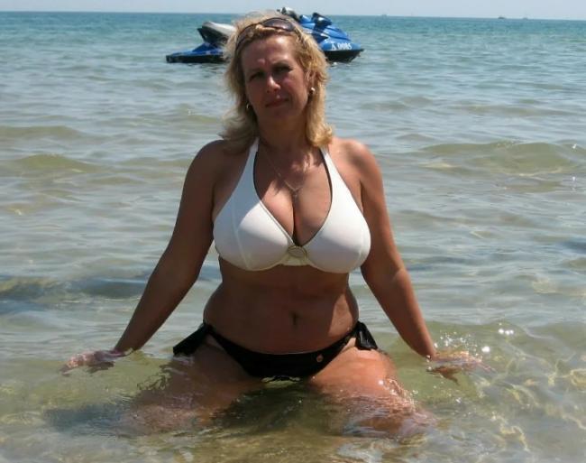 Зрелая женщина на пляже в купальнике с большими сиськами сидит на коленях в воде