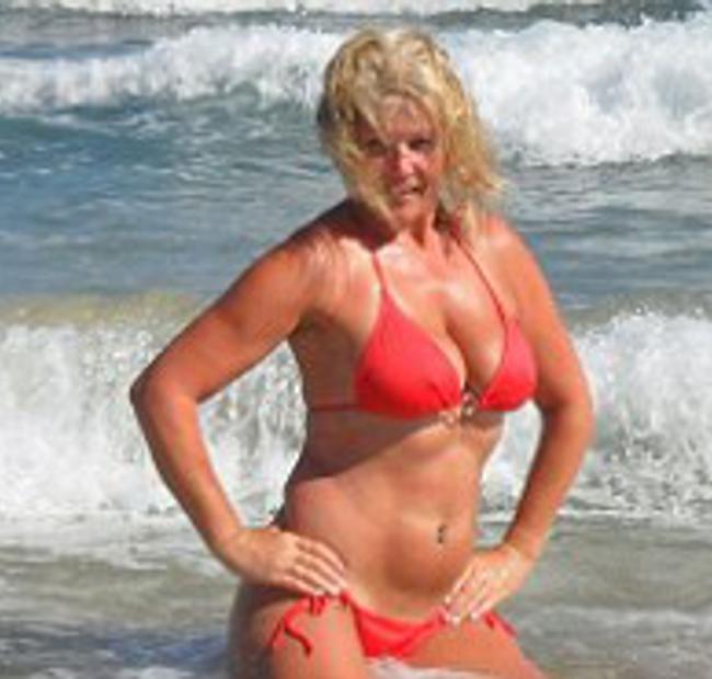 Русская зрелая блондинка в красном купальнике сидит на коленях, фото домашнее