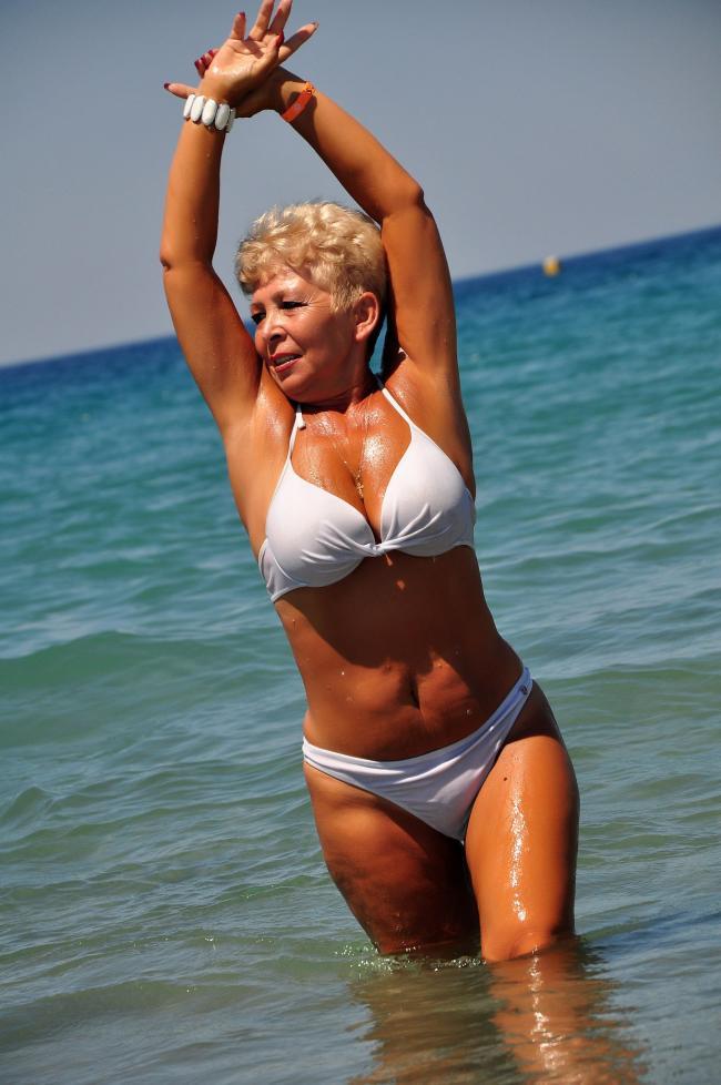 Зрелая дама за 50 с хорошей фигурой стоит по колено в воде руки подняты в белом купальнике