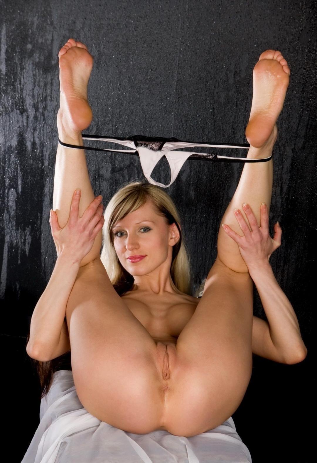 Блондинка подняла и раздвинула ножки на которых растянуты ее стринги