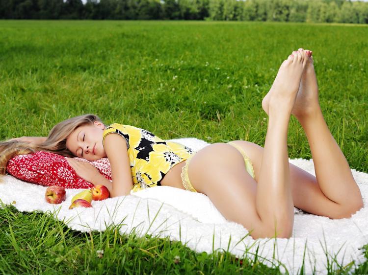 Блондинка лежит на траве на животе подняв вверх красивые голые ножки.