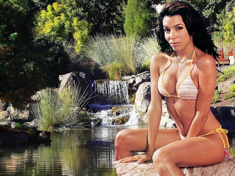 В бикини сидит на камне у водоема.