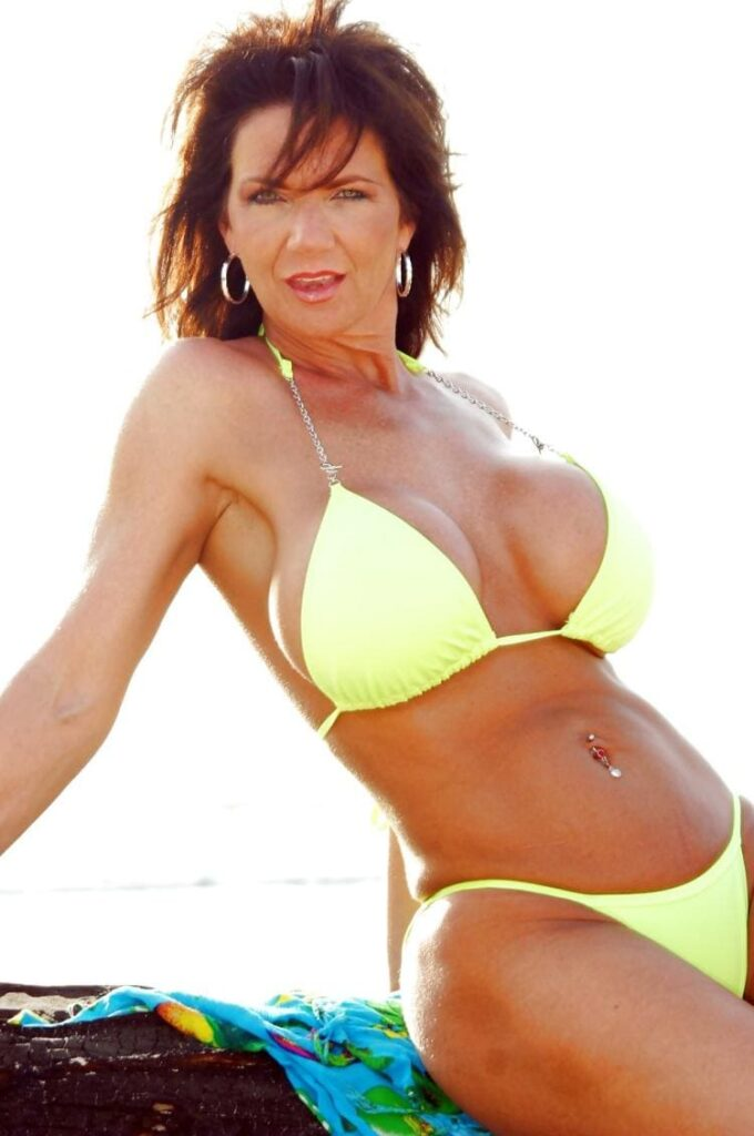 Фото зрелой женщины в купальнике желтого цвета сама сидит на камне накрытом одеждой, сиськи большие, сама приоткрыла рот и призывно смотрит улыбаясь. Волосы треплет ветер.