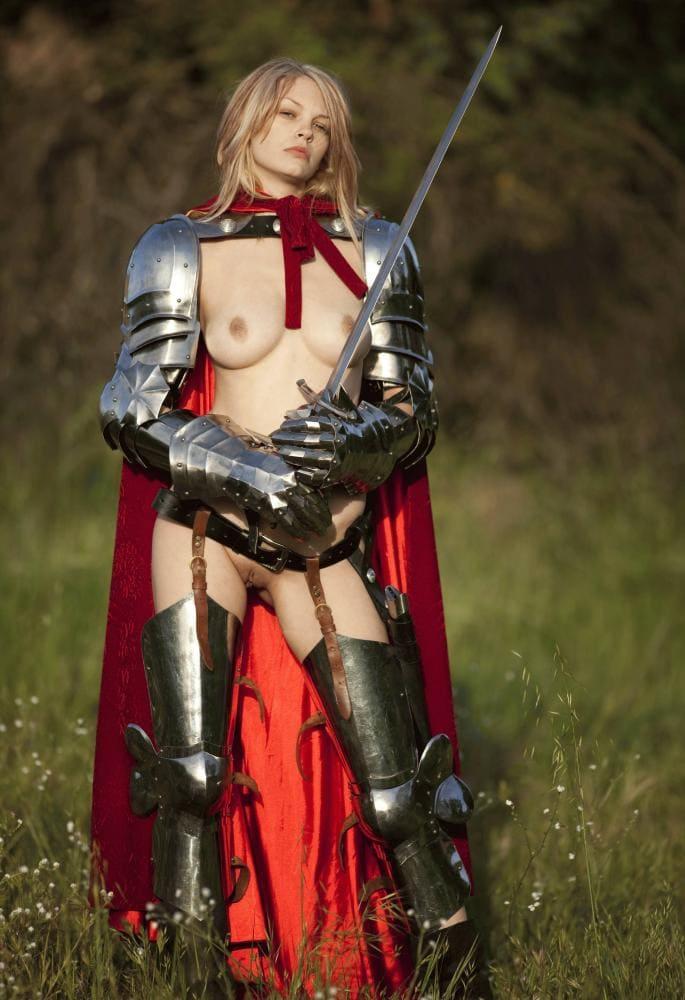 Голые девушки косплеерши фото красавицы с красивой грудью в рыцарских латах и мечем в руках, красном плаще и ботфортах, стоит на поляне, русые волосы распущены