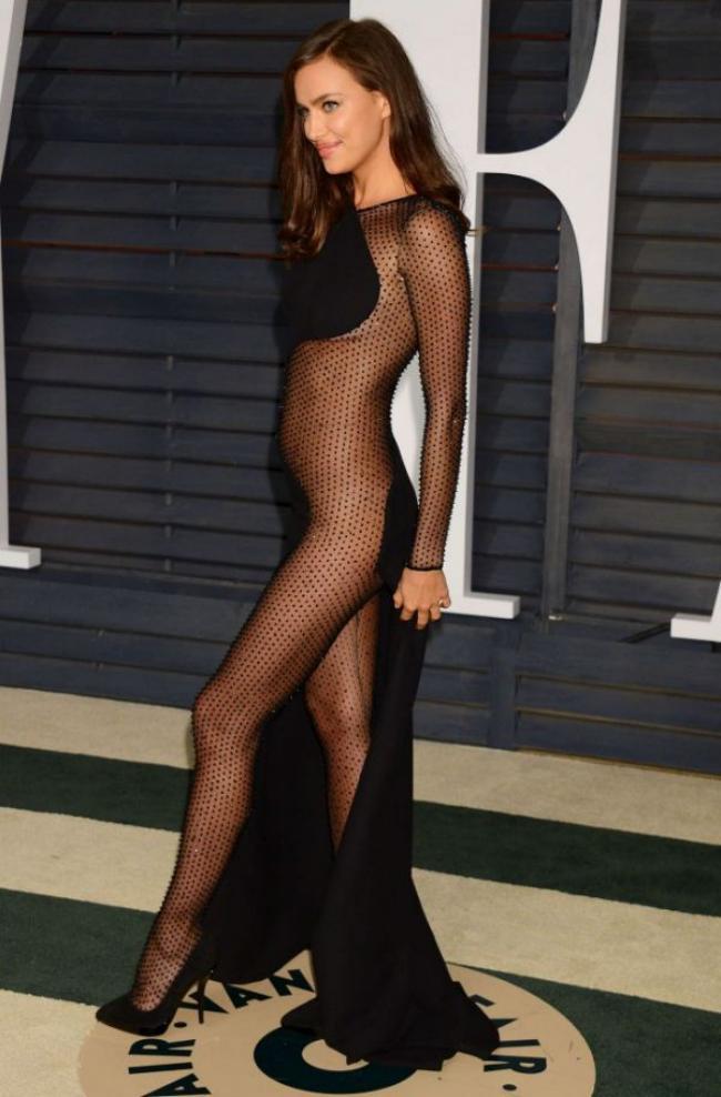 фото Ирины Шейк в шикарном прозрачном платье черного цвета, идет по подиуму в туфлях на высоком каблуке, красиво улыбается