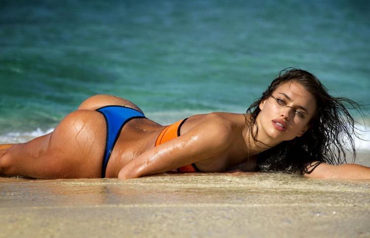 Ирина Шейк лежит на животе на берегу моря рука в трусиках.