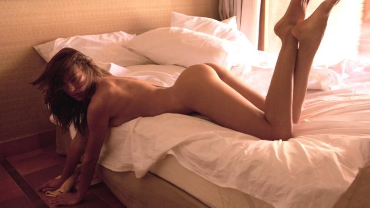 Ирина Шейк голая лежит на кровати на животе подняв свои красивые ноги.