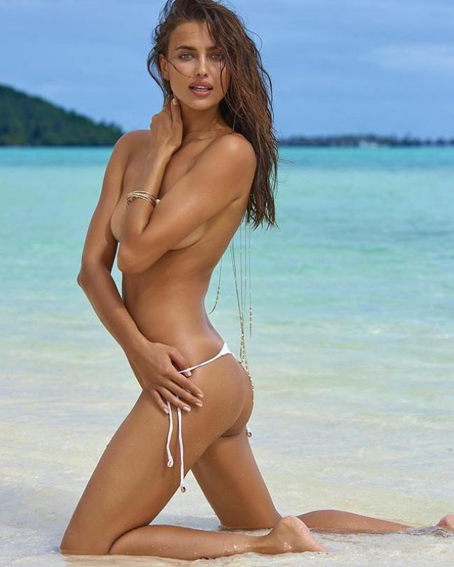 фото обнаженной Ирины Шейк, голая в бикини стоит на коленях в песке на фоне моря