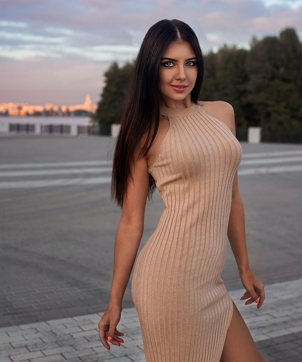 красивые девушки брюнетки стоит в обтягивающем платье с разрезом, длинные прямые волосы