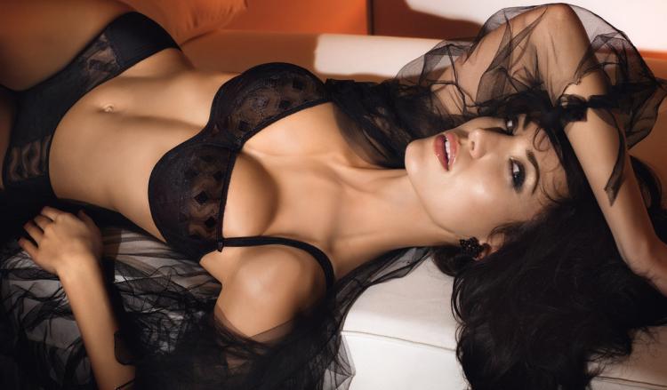 Очень красивая брбнетка в сексуальном нижнем белье лежит на кровати.