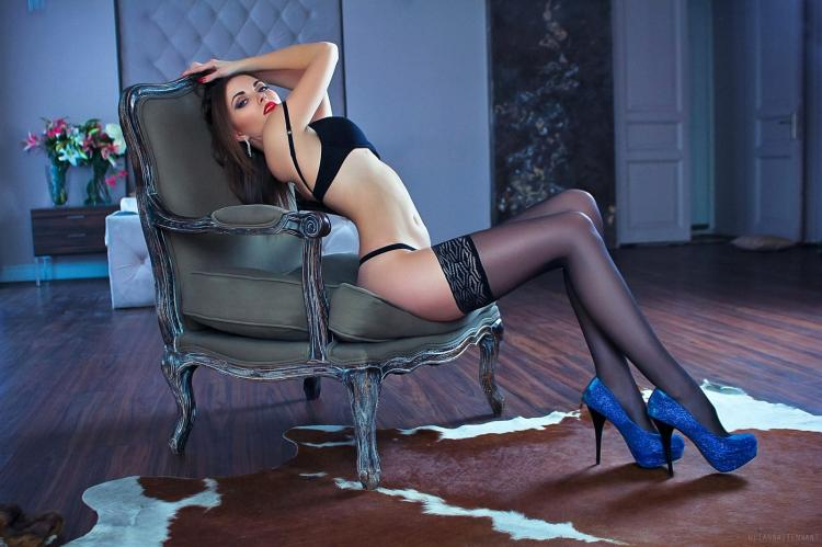 Шикарная брюнетка изогнулась в кресле, черное нижнее белье чулках туфли ярко синего цвета на высоком каблуке