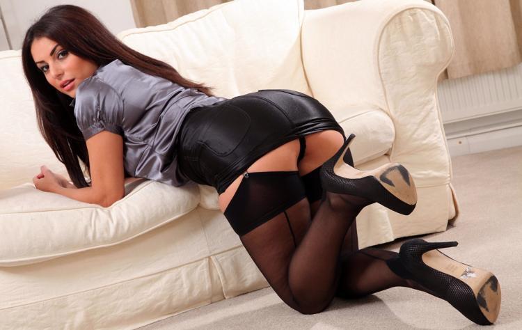 Красивая брюнетка стоит на коленях в короткой кожанной юбке. чулки туфли на высоком каблуке.