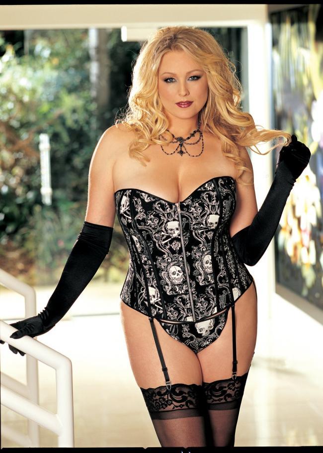 Полная красивая блондинка в черном корсете с рисунком, черные длинные перчатки. черные чулки.
