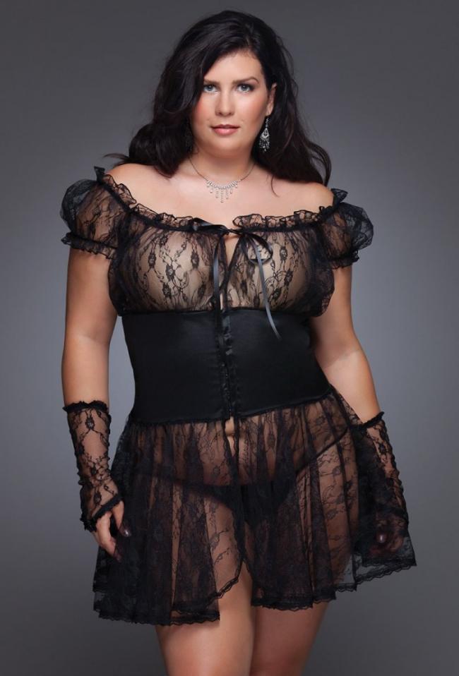 Полная девушка в черном ажурном коротком платье и перчатках с открытыми пальцами.