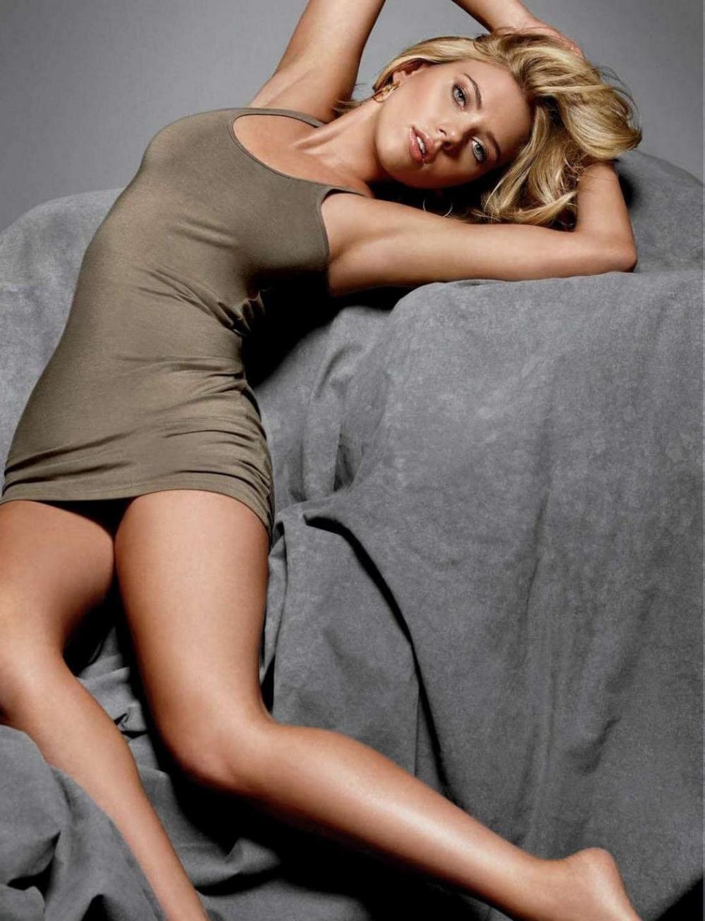 Скарлетт Йоханссон фото в коротком бутылочного цвета платье лежит на сером покрывале вся изогнулась, руки на голове