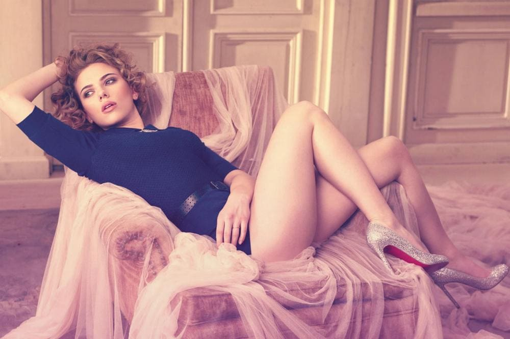 Скарлетт Йоханссон фото на кресле цвет волос шатенка, в кофточке, откинув одну руку за голову, ножки закинув на ручку согнуты в коленях на высоком каблуке светлые туфли с красной подошвой
