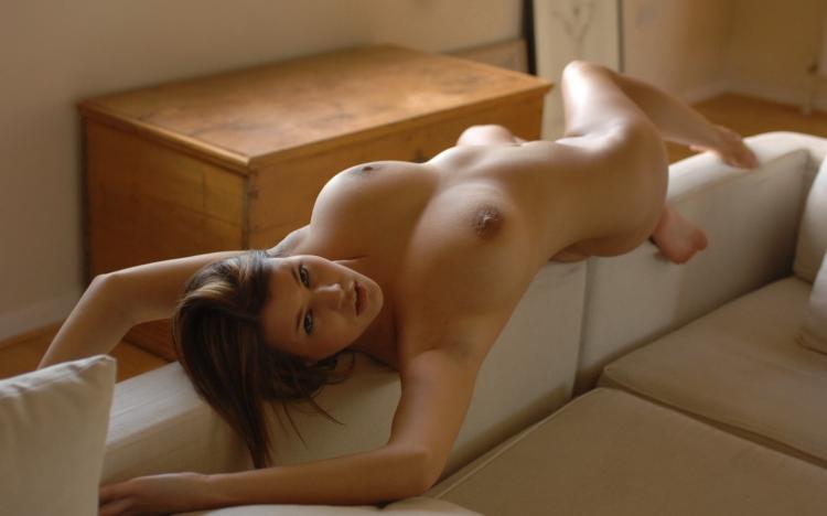 Голая лежит на диване подняв руки.