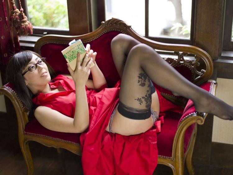 Лежит на софе в красном платье в очках, красное платье задрано, ноги в черных чулках.