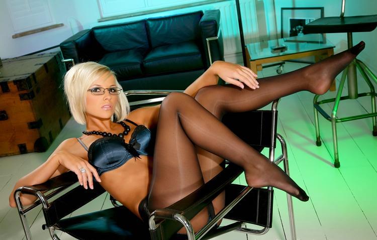 Сексуальная блондинка в очках сидит в офисном кресле, черных нейлоновых колготках, ноги задраны на ручки кресла, хорошо видны ступни