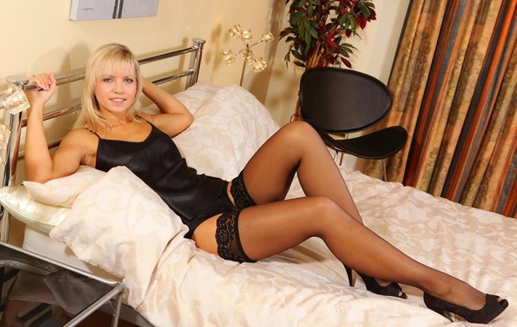 Блондинка в сексуальном белье молодая в черных чулках, туфлях на каблуке, лежит на спине на кровати, руками держится за железное изголовье кровати