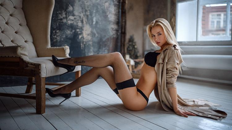 Блондинка в сексуальном белье в черном нижнем белье в чулках и туфлях на каблуке сидит на полу, вид сбоку, красивые ножки согнула в коленях