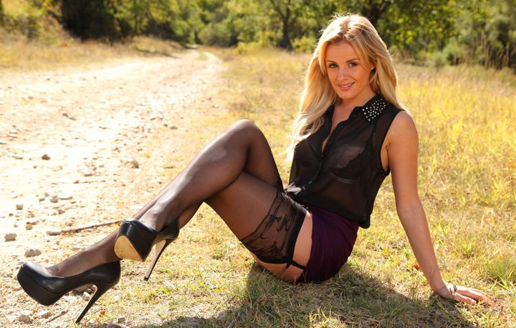 блондинка, туфли на очень высоком каблуке, чулки на поясе, сидит на земле.