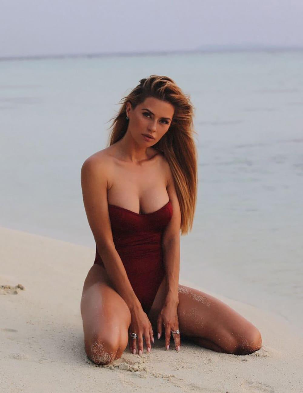 Виктория Боня горячие в закрытом купальнике с глубоким декольте сидит на песке на коленях