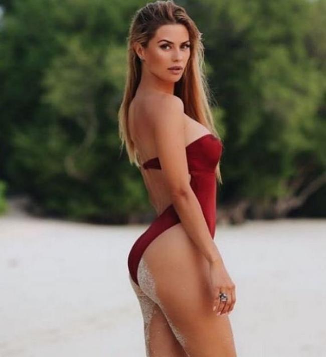 Виктория Боня фото в бордовом закрытом купальнике вполоборота стоит