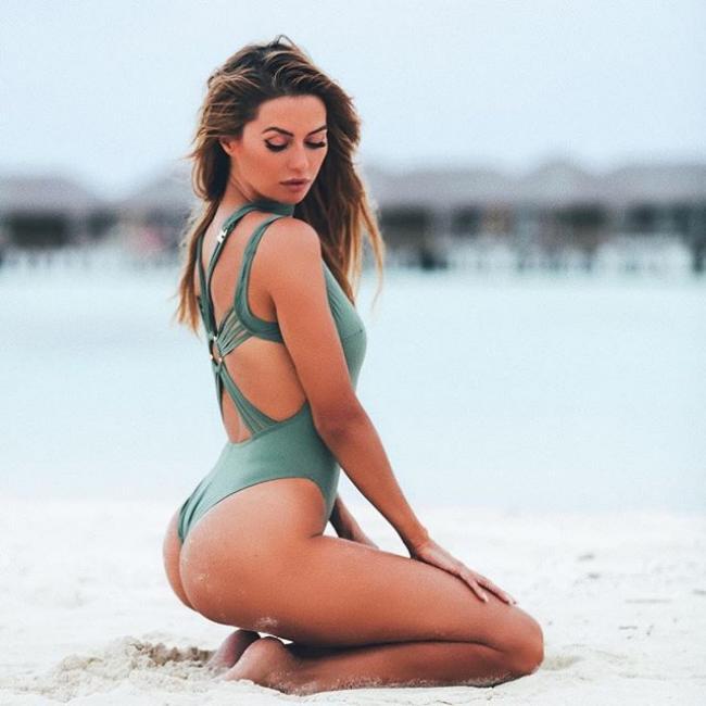 Виктория Боня горячие в закрытом купальнике бутылочного цвета сидит на ногах в песке