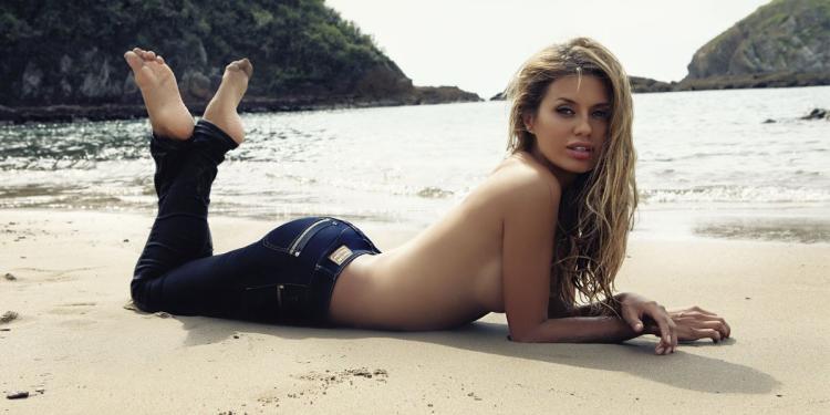 Виктория Боня лежит на пляже на животе в джинсах грудь голая ноги подняты кверху