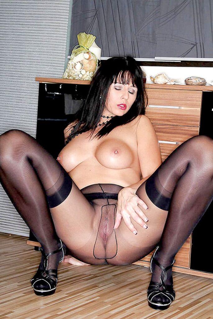 фото зрелых мамок в колготках женщина сидит на полу голая, широко раздвинув ноги демонстрируя бритую пизду через черные колготки, красивая грудь вздымается, глаза закрыты, похотливый рот приоткрыт