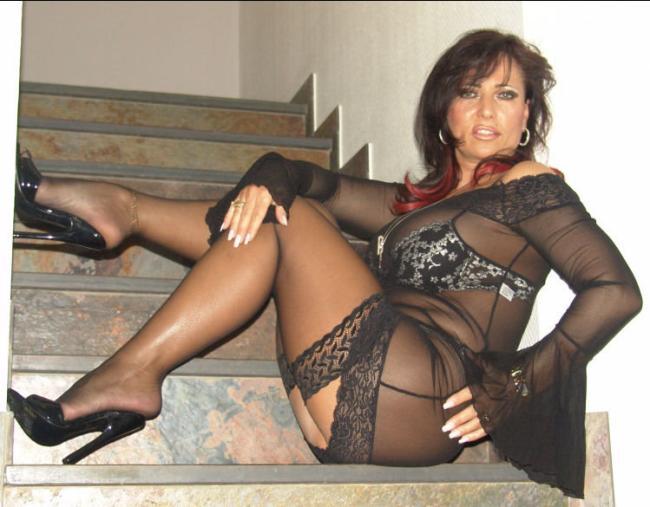 Шикарная зрелая шатенка сидит на лестнице в прозрачном платье в черных чулках,, босоножки высокий каблук.