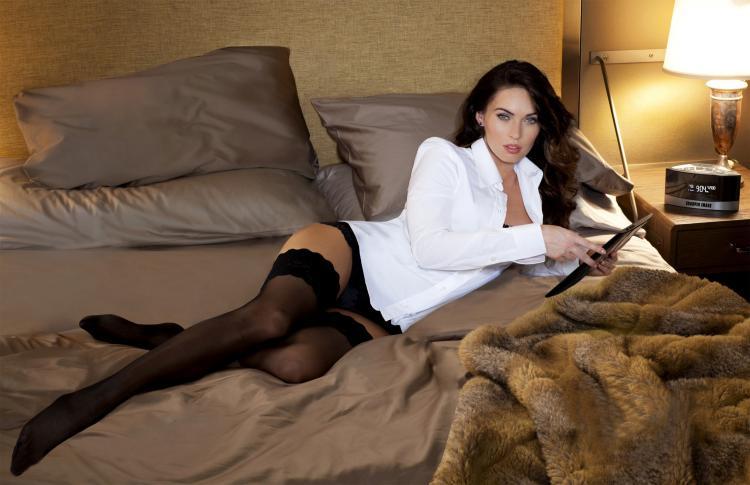 Красивая брюнетка в белой рубашке и черных чулках лежит на кровати