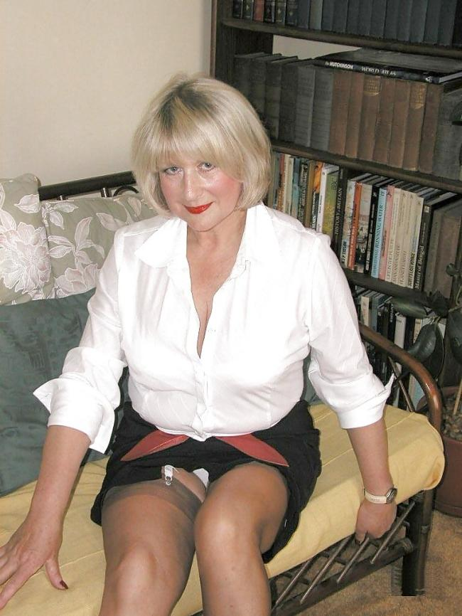 Блондинка за 50 сидит в короткой черной юбке, похотливо смотрит на нас