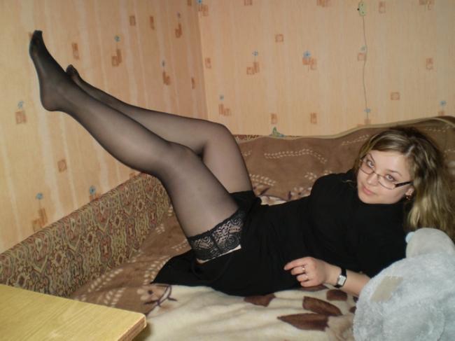 Зрелая в очках в чулках лежит на кровати задрав ноги на стену