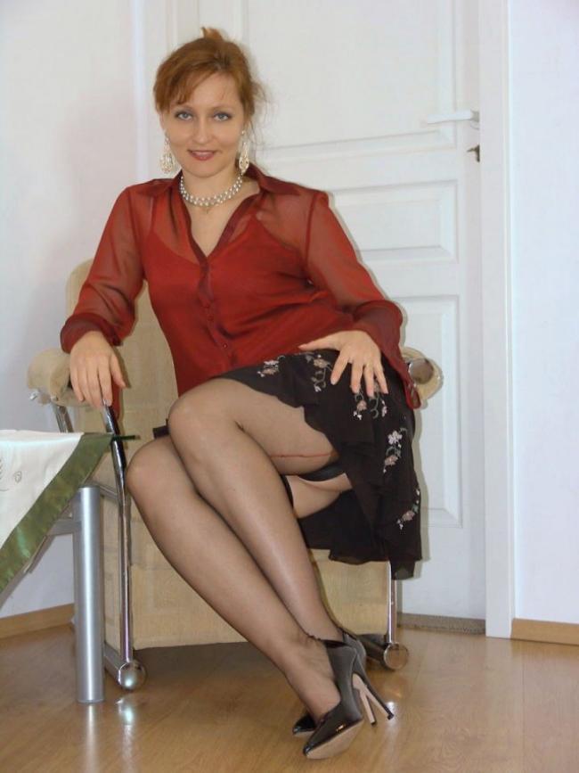 Сидит в кресле показывая свои красивые ножки в чулках