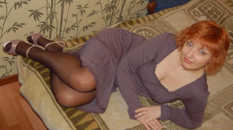 Рыжая зрелая лежит на кровати на боку в капроне, глубокое декольте