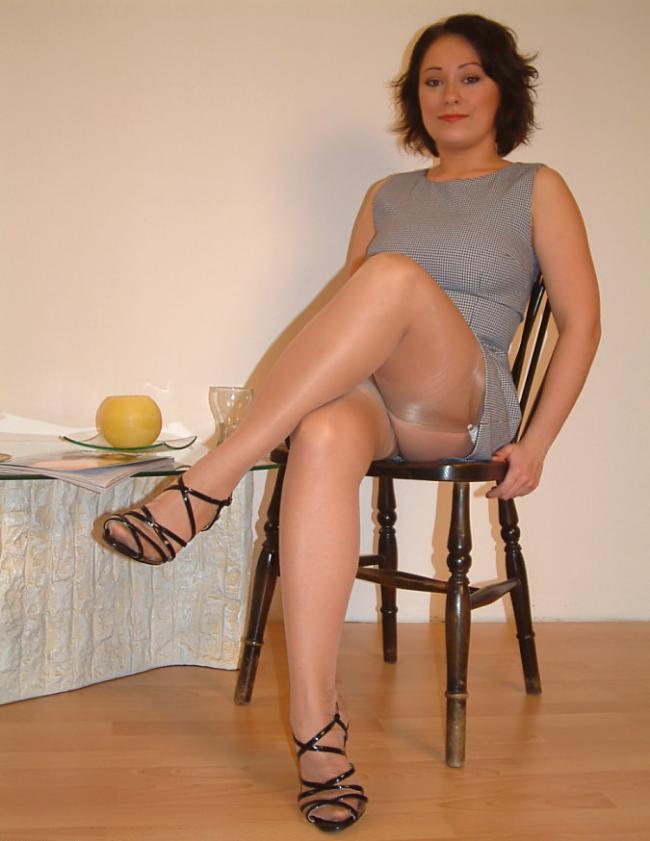 Красивая шатенка сидит на стуле вид шикарных ног в капроновых светлых чулках