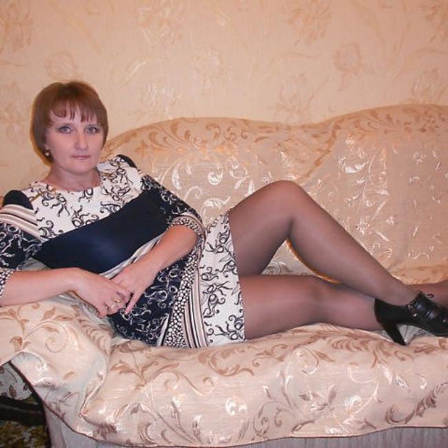 Зрелая с короткой стрижкой полулежит в постнли в капроновых колготках